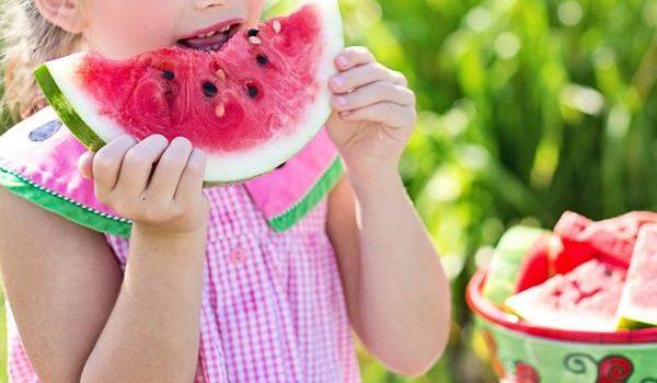 bambina mangia anguria in estate